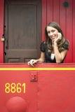Frau, die auf Geländer im roten Zug-Kombüsen-Auto sich lehnt stockbilder
