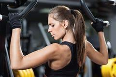 Frau, die auf Gewichthebenmaschine trainiert Lizenzfreie Stockfotografie