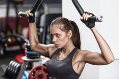 Frau, die auf Gewichthebenmaschine trainiert Lizenzfreie Stockfotos