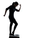 Frau, die auf glücklichem Schattenbild der Gewichtsskala steht Stockfoto