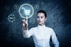 Frau, die auf glühende Warenkorb-Ikone zeigt Stockfotografie
