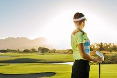 Frau, die auf Golfplatz an einem sonnigen Tag steht Stockfotos