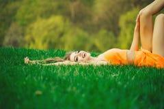 Frau, die auf grünem Gras liegt stockfotografie