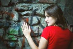 Frau, die auf Graffitiwand sich lehnt Lizenzfreies Stockbild