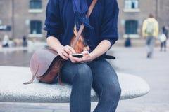 Frau, die auf Granitbank unter Verwendung des intelligenten Telefons sitzt Stockfotografie