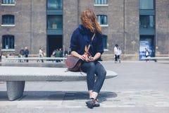 Frau, die auf Granitbank unter Verwendung des intelligenten Telefons sitzt Stockfoto