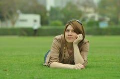 Frau, die auf Gras liegt Stockbilder