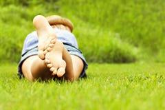 Frau, die auf Gras liegt Lizenzfreie Stockfotos