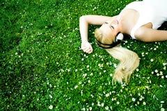 Frau, die auf Gras liegt Stockfotos