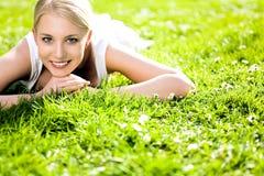 Frau, die auf Gras liegt Lizenzfreies Stockfoto