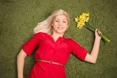 Frau, die auf Gras liegt und ein Bündel Tulpen hält Stockfoto