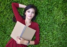 Frau, die auf Gras mit Buch liegt stockfoto