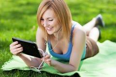 Frau, die auf Gras mit digitaler Tablette liegt Stockbild