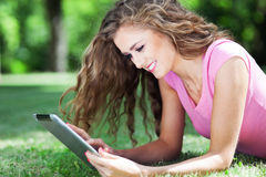 Frau, die auf Gras mit digitaler Tablette liegt Stockfotos