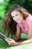 Frau, die auf Gras mit digitaler Tablette liegt Stockfotografie