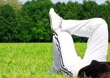 Frau, die auf Gras sich entspannt Lizenzfreie Stockfotos