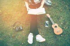 Frau, die auf Gras sich entspannt Stockfoto