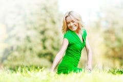 Frau, die auf Gras sitzt Stockfotografie