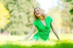 Frau, die auf Gras sitzt Lizenzfreies Stockfoto