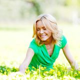 Frau, die auf Gras sitzt Lizenzfreie Stockfotos