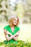 Frau, die auf Gras sitzt Stockbild