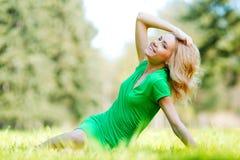 Frau, die auf Gras sitzt Stockfoto