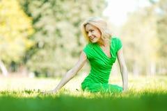 Frau, die auf Gras sitzt Stockfotos