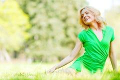 Frau, die auf Gras sitzt Stockbilder