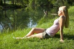 Frau, die auf Gras sitzt Lizenzfreie Stockbilder