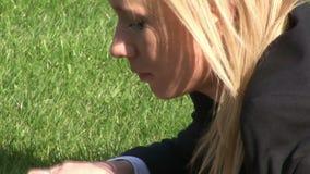 Frau, die auf Gras unter Verwendung der Laptop-Computers liegt stock footage