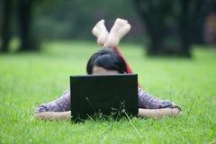 Frau, die auf Gras unter Verwendung des Laptops legt Stockbild
