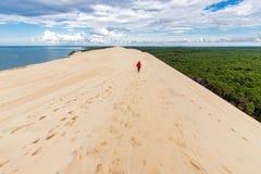 Frau, die auf große Sanddüne geht stockfoto