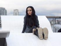 Frau, die auf großem weißes MetallKlubsessel sitzt lizenzfreies stockbild