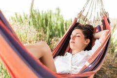 Frau, die auf Hängematte schläft lizenzfreie stockbilder