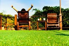 Frau, die auf hölzernem sunbed auf grünem künstlichem Gras sich entspannt und den blauen Himmel schaut Lizenzfreies Stockfoto