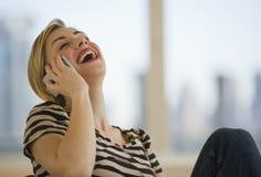 Frau, die auf Handy lacht Lizenzfreie Stockfotografie
