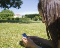 Frau, die auf Handy texting ist Stockfoto