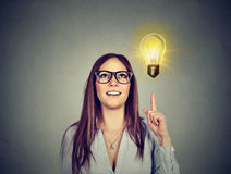 Frau, die auf helle Glühlampe zeigt Wachsendes Geschäftskonzept des Erfolgs lizenzfreies stockbild