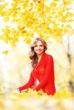 Frau, die auf Herbstlaub sitzt Lizenzfreies Stockbild