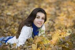 Frau, die auf herbstlichen Blättern liegt Lizenzfreies Stockfoto