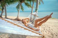 Frau, die auf Hängematte sich entspannt Lizenzfreie Stockfotografie