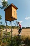 Frau, die auf Hochstand für Jäger klettert stockfoto