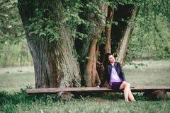 Frau, die auf Holzbank unter enormem Baum sitzt Mädchen, das sich achtern entspannt Stockbilder