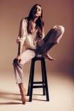 Frau, die auf Holzstuhl in der Spitze und in den Hosen sitzt Stockfotos