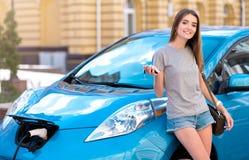 Frau, die auf ihr Elektroauto stützt Lizenzfreies Stockbild