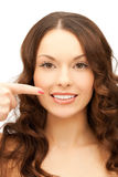 Frau, die auf ihr toothy Lächeln zeigt Stockbild