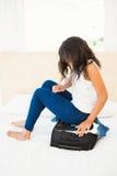 Frau, die auf ihrem übervollen Koffer sitzt Lizenzfreie Stockfotografie