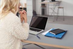 Frau, die auf ihrem Ellbogen an ihrem Schreibtisch mit Material sich lehnt Stockbilder