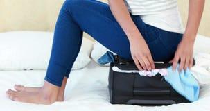Frau, die auf ihrem Gepäck sitzt stock footage