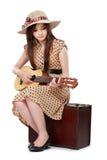 Frau, die auf ihrem Koffer beim Spielen der Gitarre sitzt Stockbild